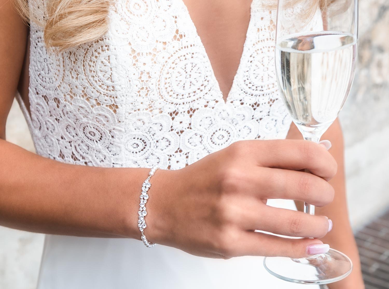 Bruid draagt een prachtige armband met parels om de pols voor een complete look