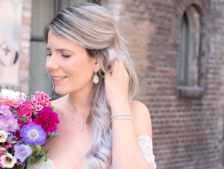 Vrouw draagt bruidssieraden set met parels en bloemen