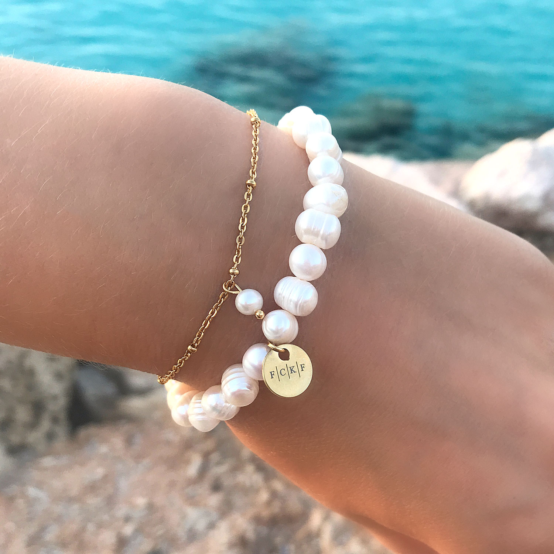 Gouden minimalistische parel armband om de pols samen met grove parel armband