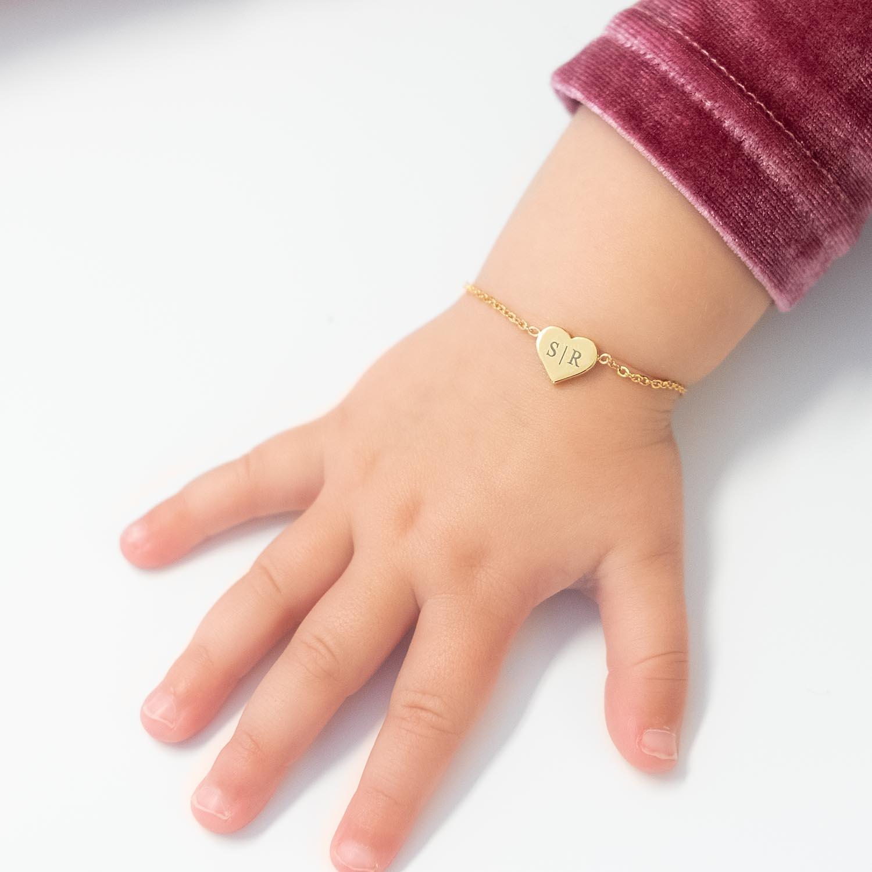 Gouden hartjes armband om de pols met gravering