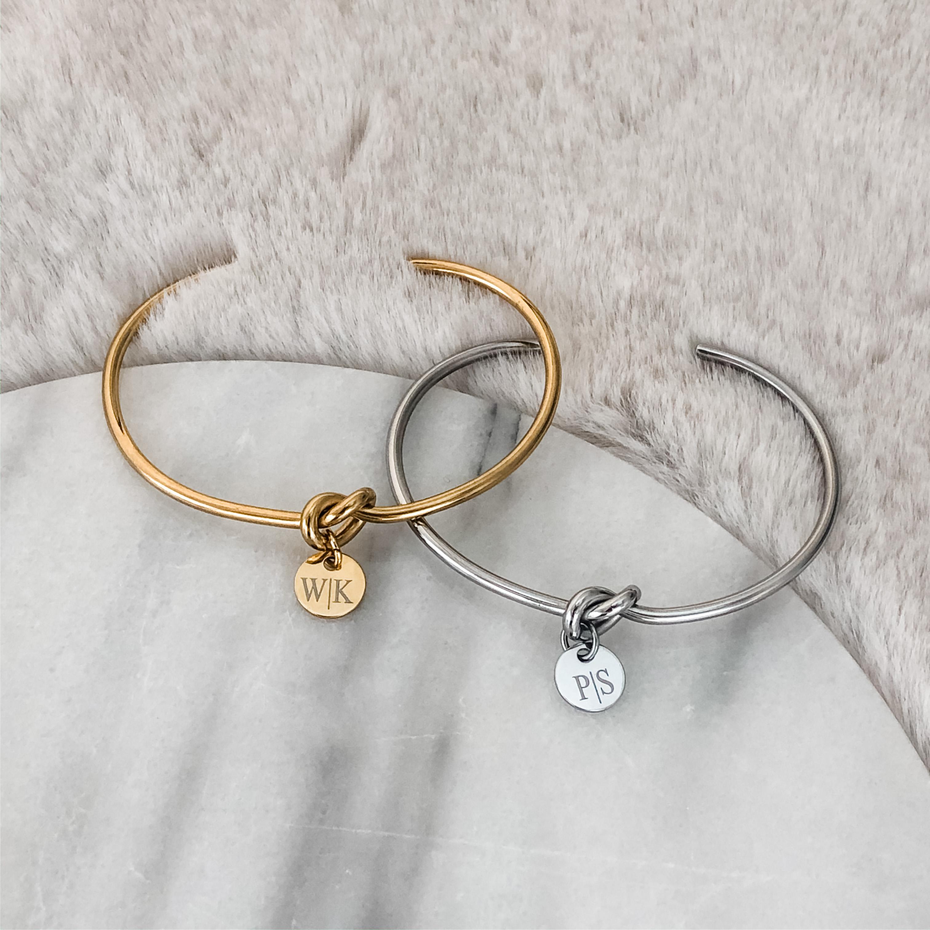 Knoop armband in het goud en zilver op een marmeren plaatje
