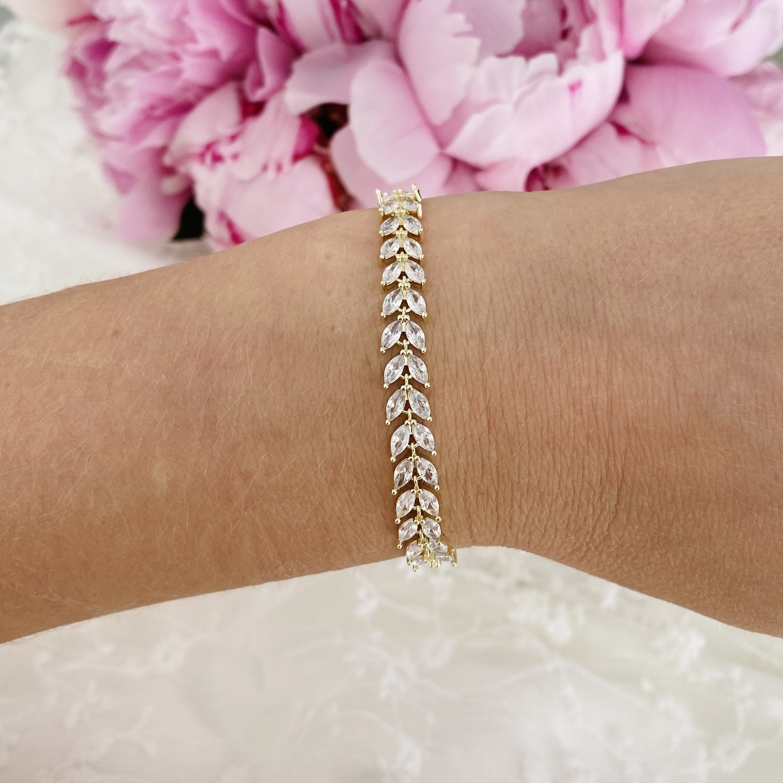 vrouw draagt goud kleurige bruids armband om pols