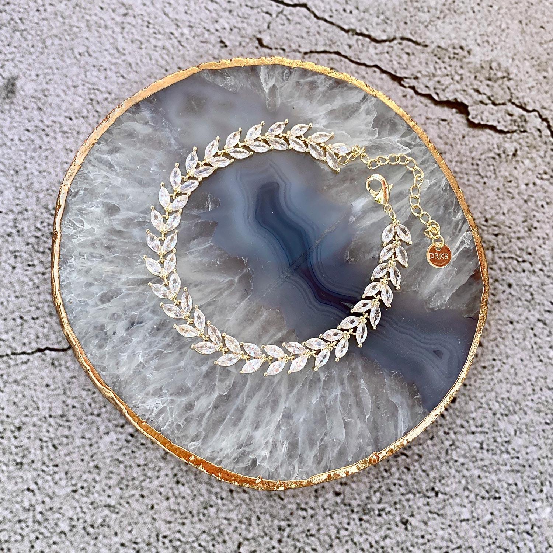 Mooie goudkleurige sieraden op een marmer plaatje om te kopen
