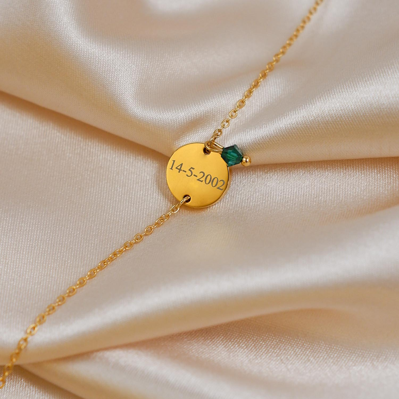 Gouden birthstone armband op satijnen ondergrond