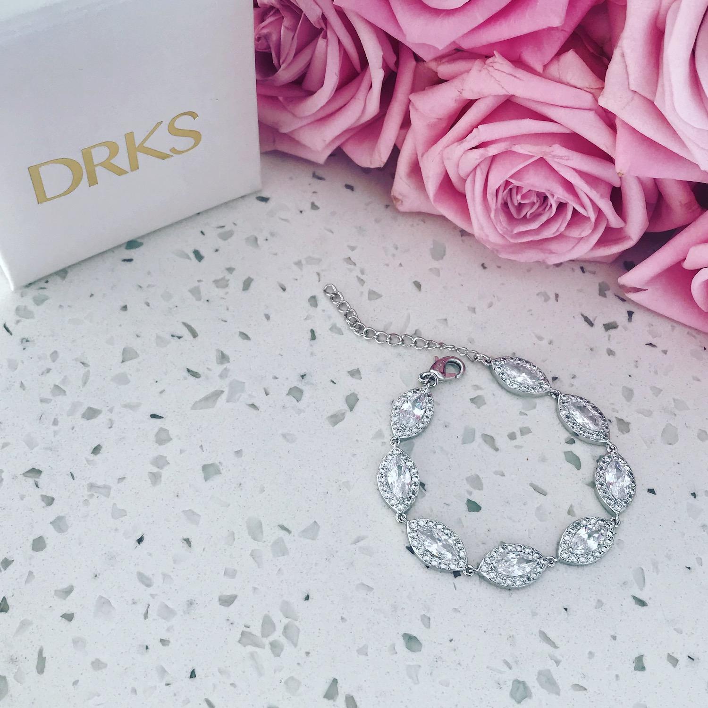 Mooie zilveren sparkle armband op marmeren plaatje met rozen
