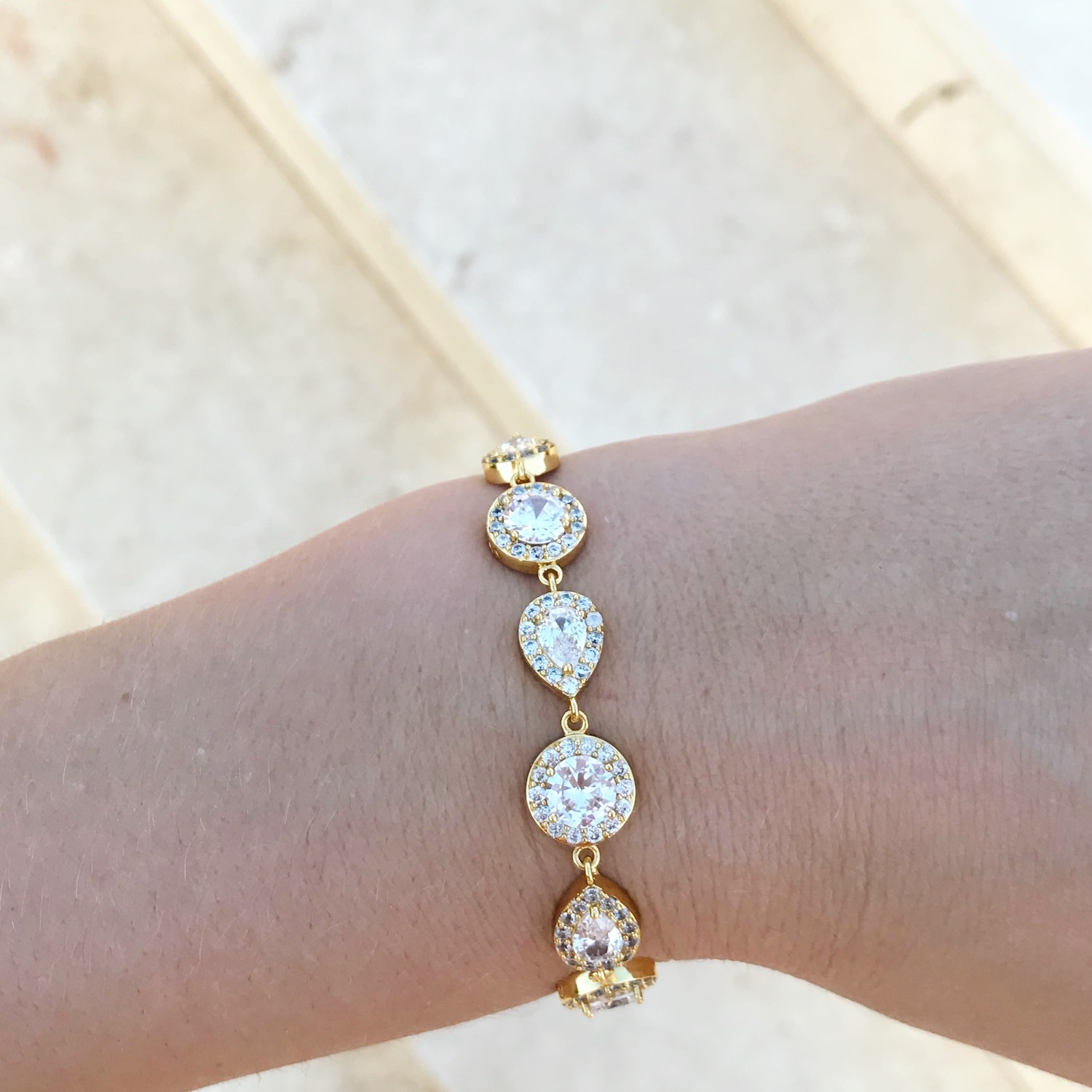 Woman wearing luxurious bracelet in gold with zirconia