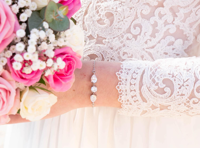 Vrouw met bloemen in bruidsjurk met mooie armband