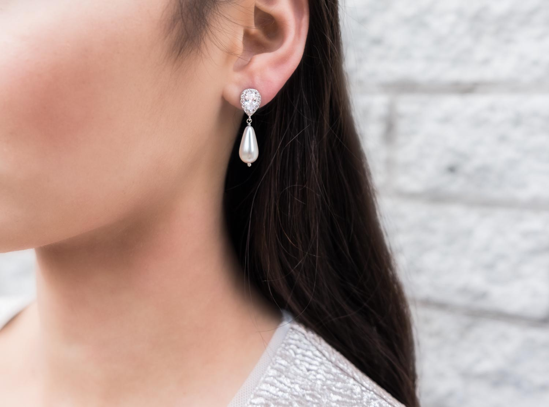 vrouw met donkere haren draagt de faux pearl oorbellen in haar oor