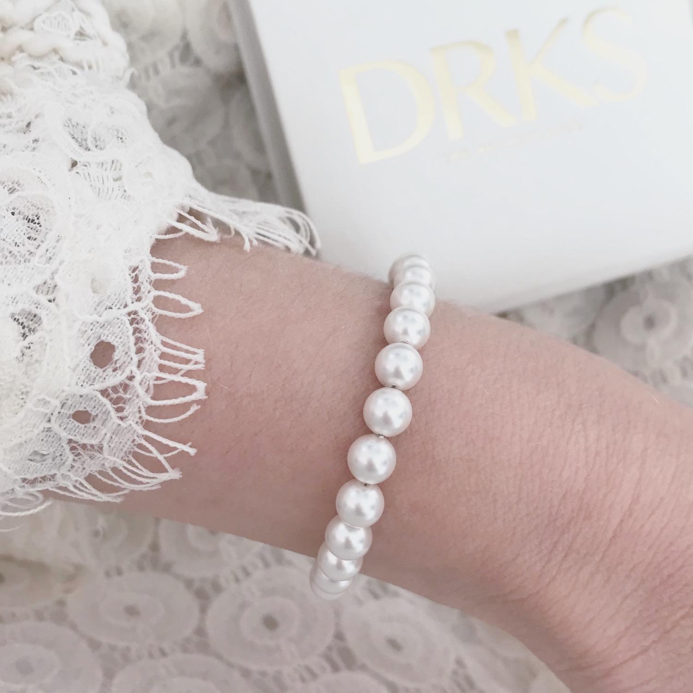 Vrouw met een ivoor faux pearls armband van DRKS