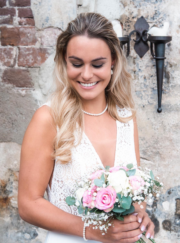 Bruid draagt de faux pearl ketting om de hals voor een complete look