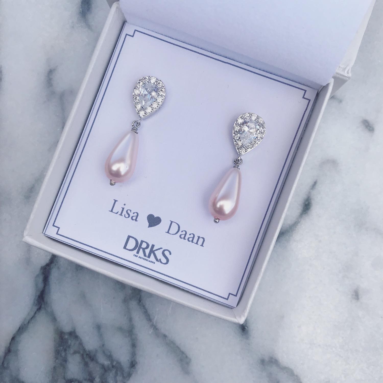 Elegante oorbellen van DRKS met roze faux pearls in sieradendoosje