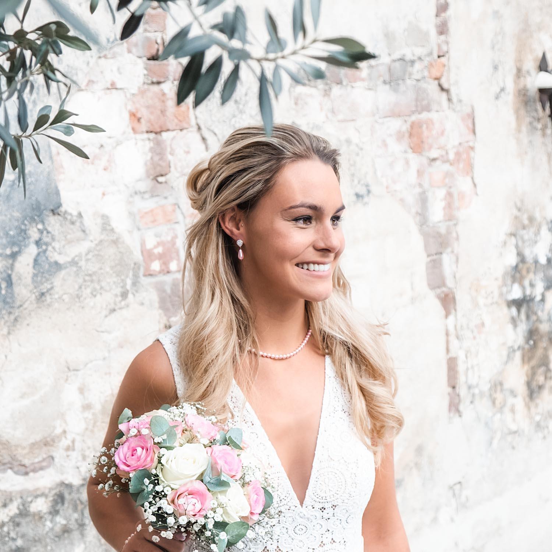 Bruid draagt roze faux pearl oorbellen met een ketting