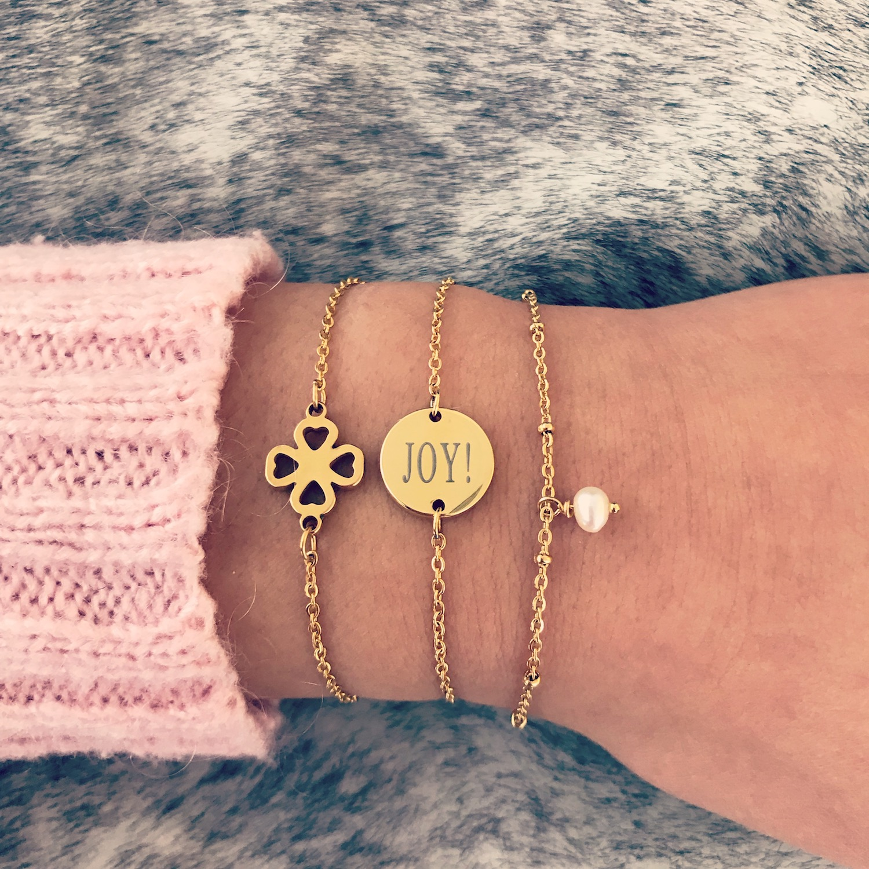 Gouden armbandjes met roze trui op vachtje