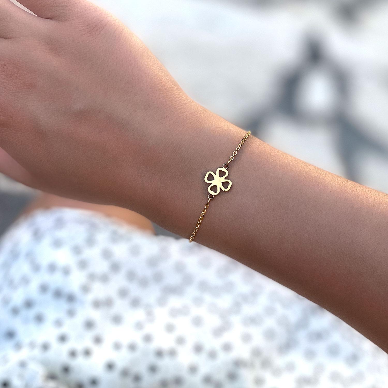 Mooi klavertje armband bij een jonge vrouw om de pols