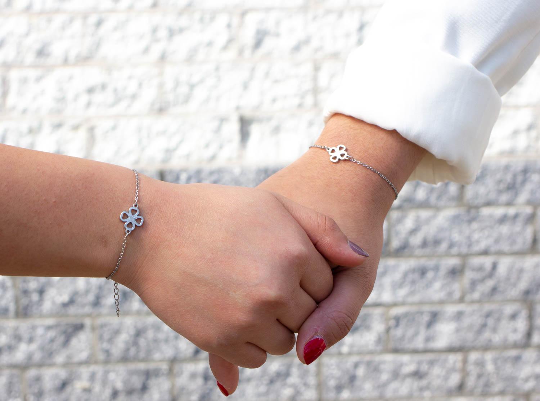 Moeder en dochter houden handen vast met sieraad