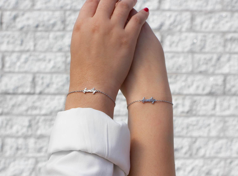 Moeder en dochter met een matchende armband met family