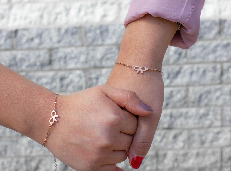 Moeder en dochter dragen rose gouden armband met strikje