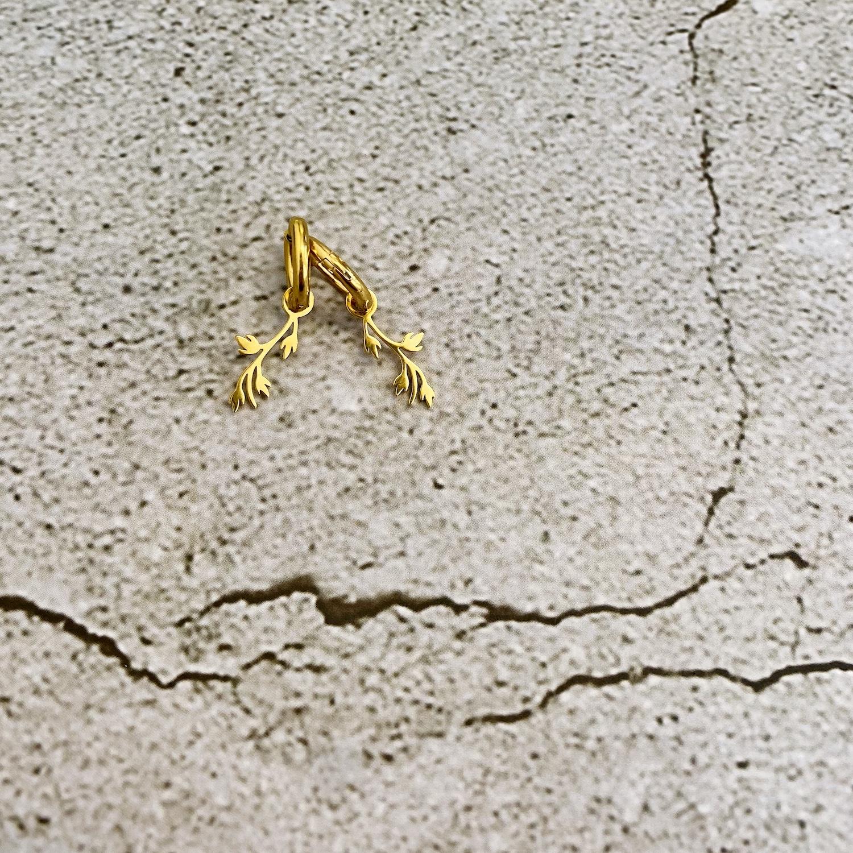 Gouden oorringetjes met leaves op stenen ondergrond