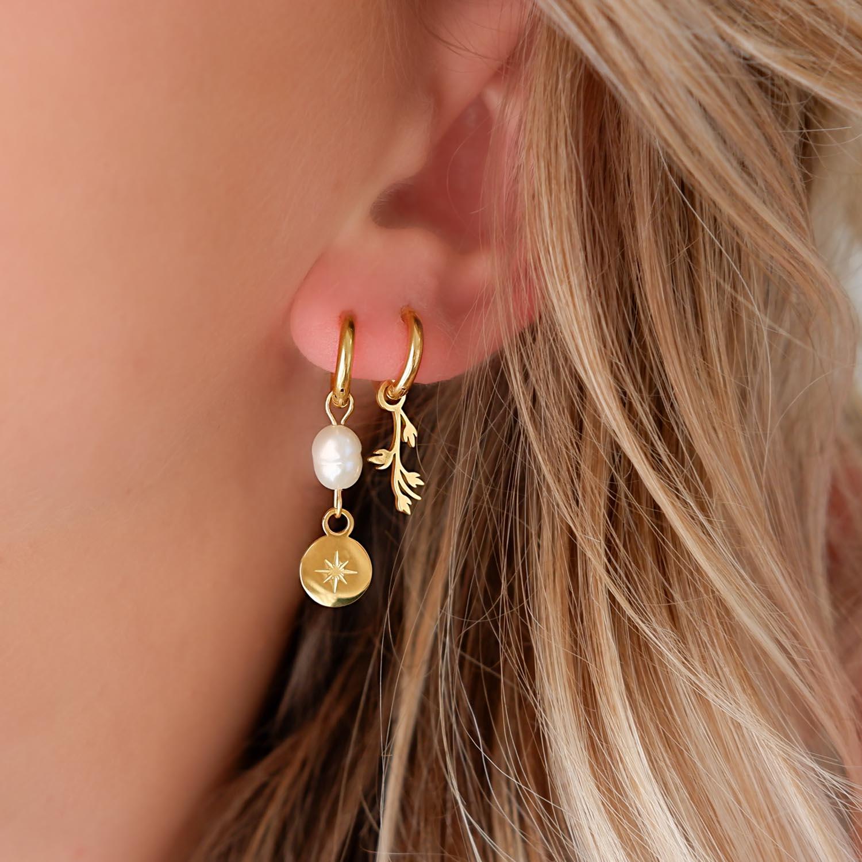 Mooie oorbellen met parels in het oor voor een trendy look
