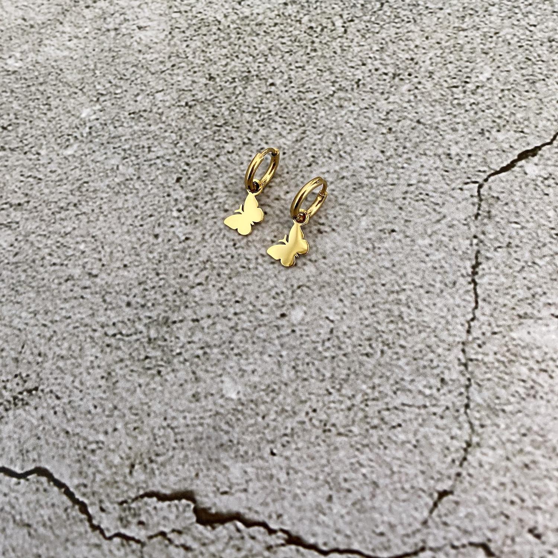 Gouden vlinder oorbellen op stenen ondergrond