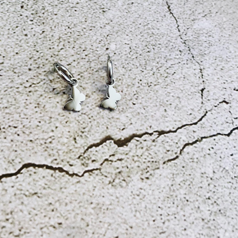 Zilveren vlinder oorringetjes op stenen ondergrond