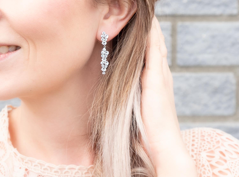 Vrouw draagt elegante lange oorbellen in het zilver