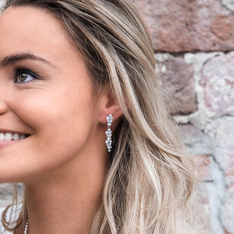 Vrouw draagt mooie sparkle oorbellen in het oor voor een mooie look