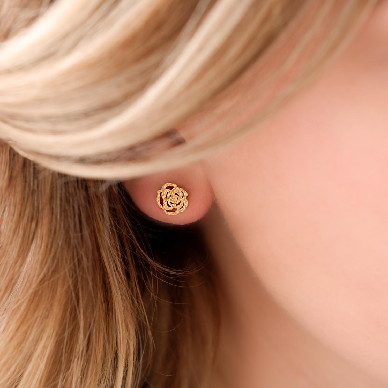 Meisje draagt goud roosjes oorbellen