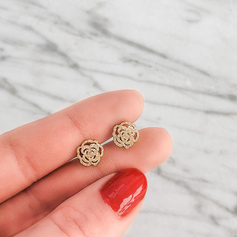 gouden oorbellen met een roos in de hand voor een trendy ook