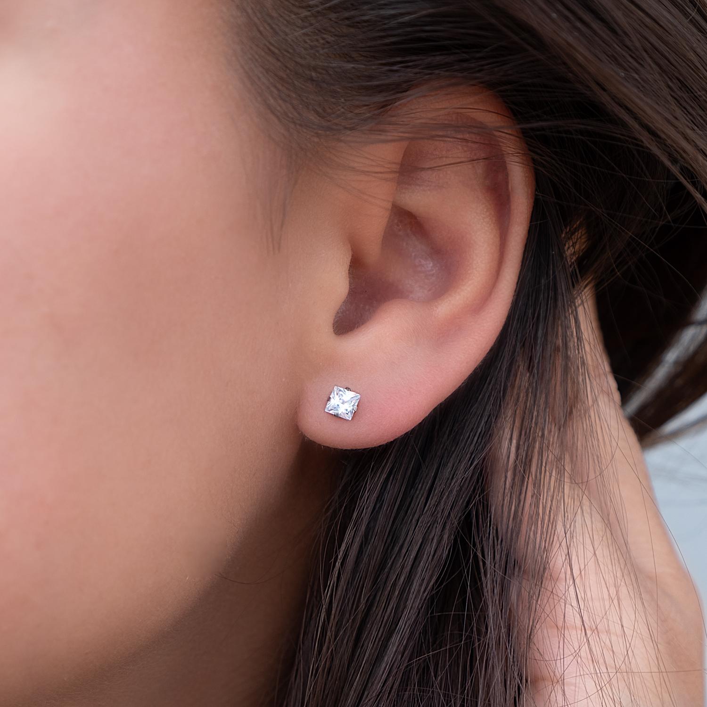 Vrouw draagt sparkle oorknopjes in het oor als minimalistische trend