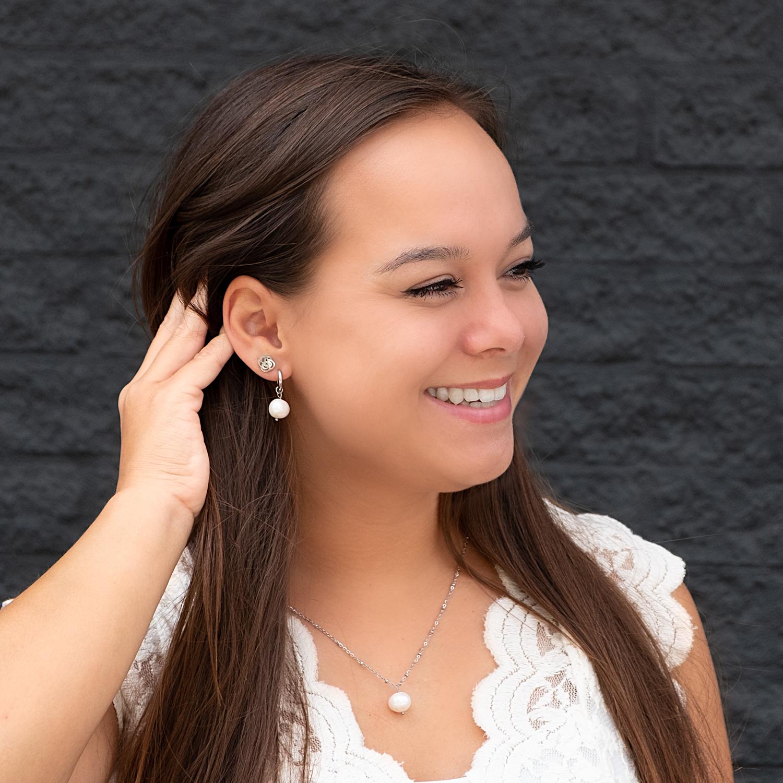 Vrouw draagt parel oorbellen samen met parel ketting in combinatie