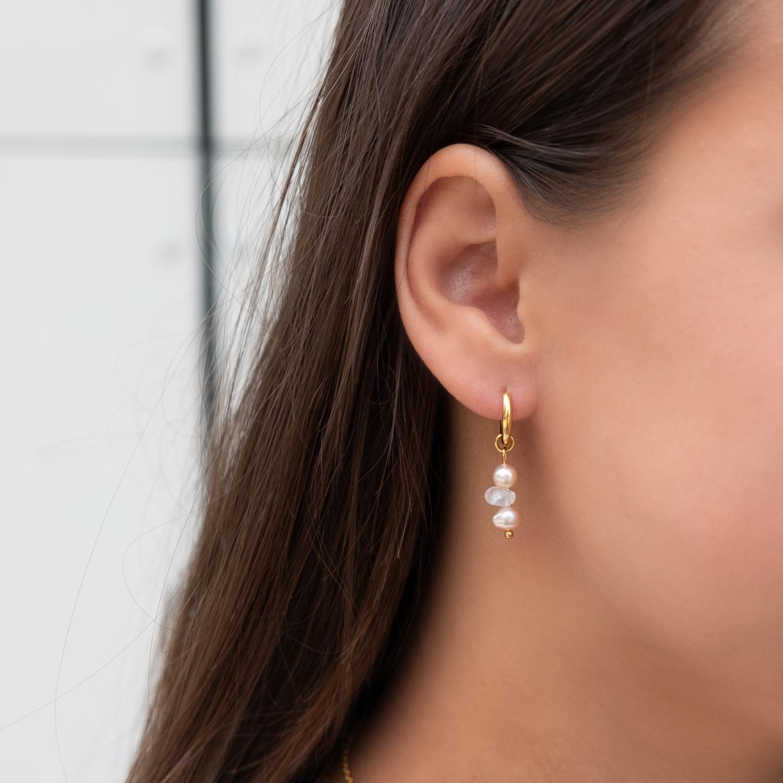Vrouw draagt oorringetjes met parel in het oor met rozenkwarts