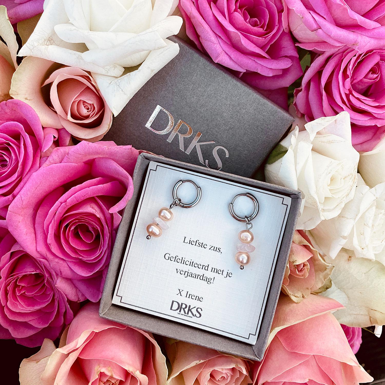 Leuke oorbellen met rozenkwarts in een sieradendoosje