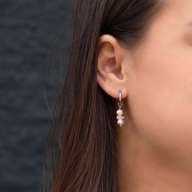 Vrouw draagt parel oorbellen met rosequartz in het oor