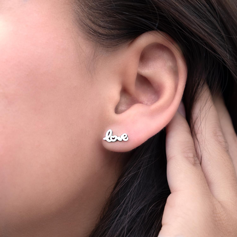 Zilveren stud oorbellen in het oor bij een vrouw met donker haar