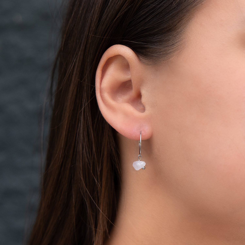 Trendy zilveren oorringetjes in het oor bij donker haar