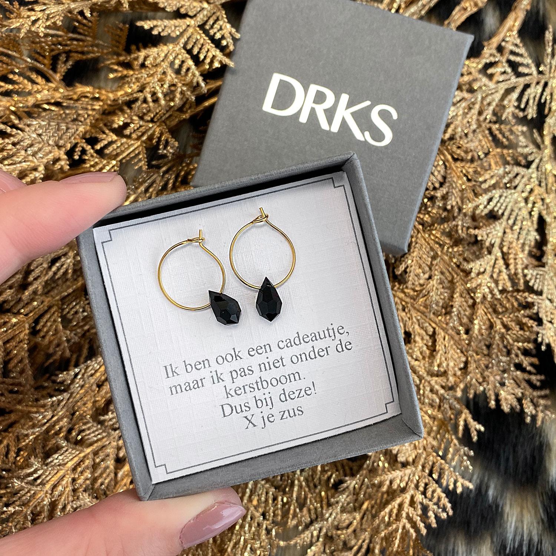 Gouden oorringetjes met een zwart hangertje als steentje