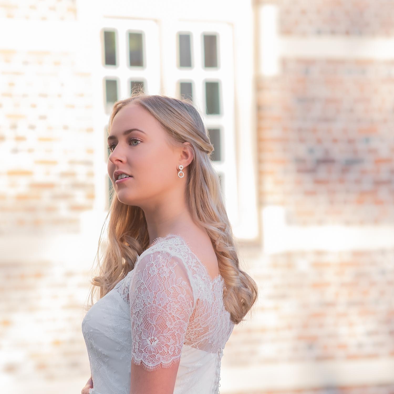 Bruid draagt minimalistische oorbellen in het oor voor bruidslool
