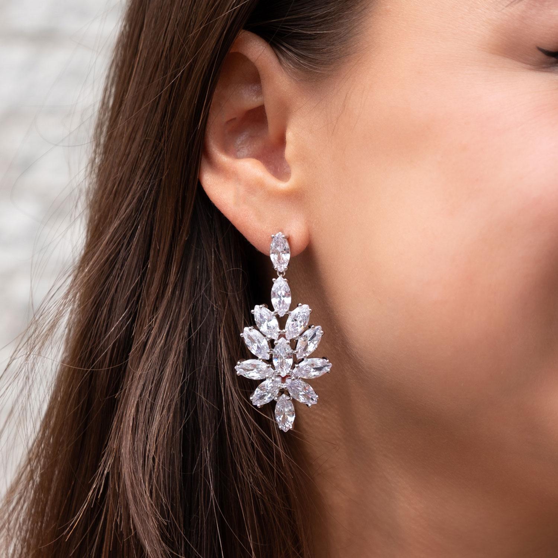 Vrouw draagt grote zilveren statement oorbellen voor de bruid