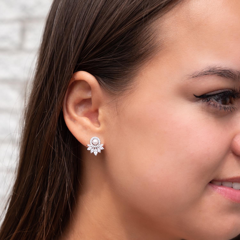 Vrouw draagt pareloorbellen voor de bruid in het oor