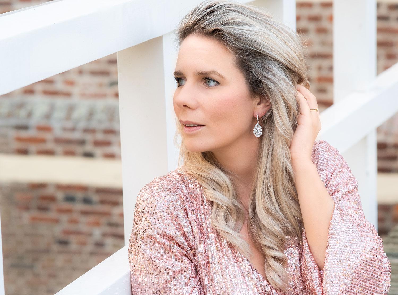 Vrouw draagt mooie bruidsoorbellen met steentjes en parels voor een prachtige look