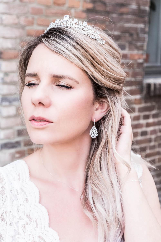 Bruid draagt haaraccessoire met kroon en parels en oorbellen