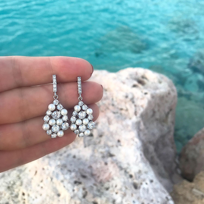 Mooie oorbellen met parels in de hand en steentjes