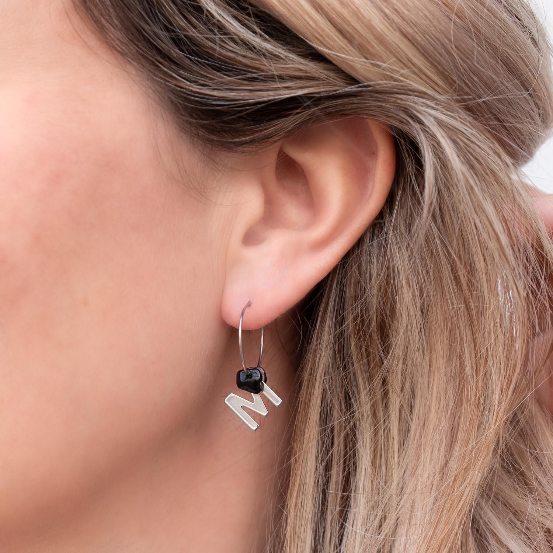 Zilveren oorringetjes met letter en steen in het oor bij blond haar