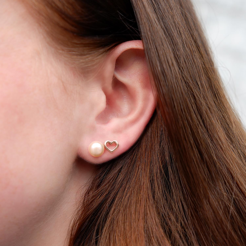 rose kleurige oorbellen met hartje in het oor samen met de parel oorbellen