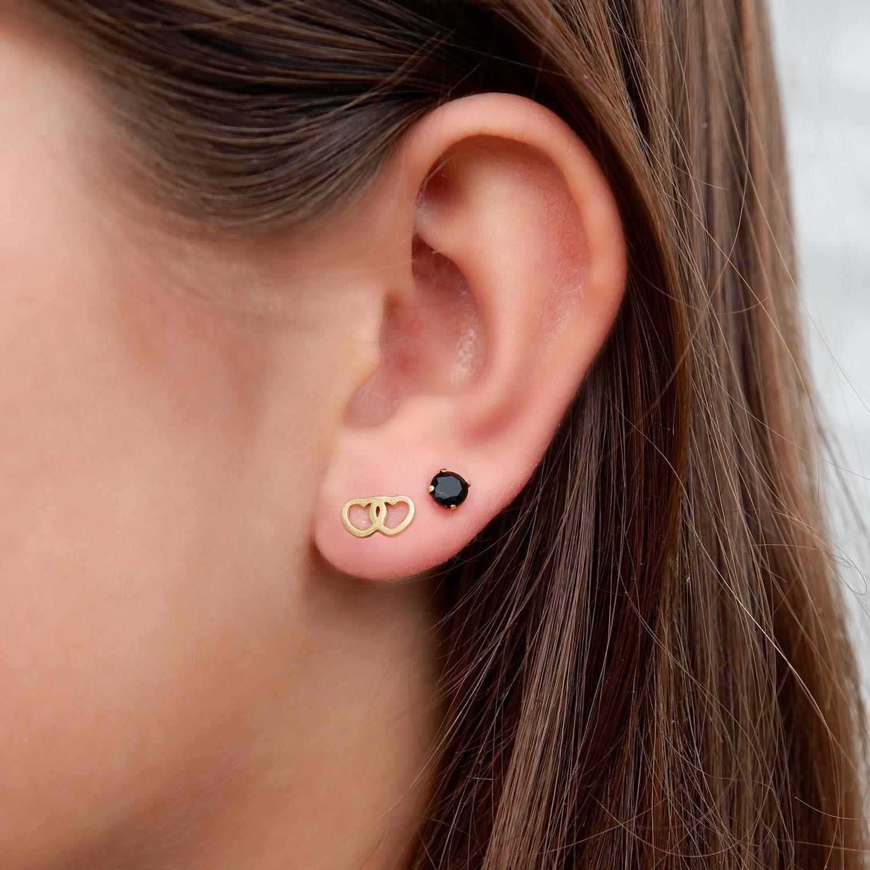 Gouden oorbellen met hartjes in het oor bij een jonge vrouw