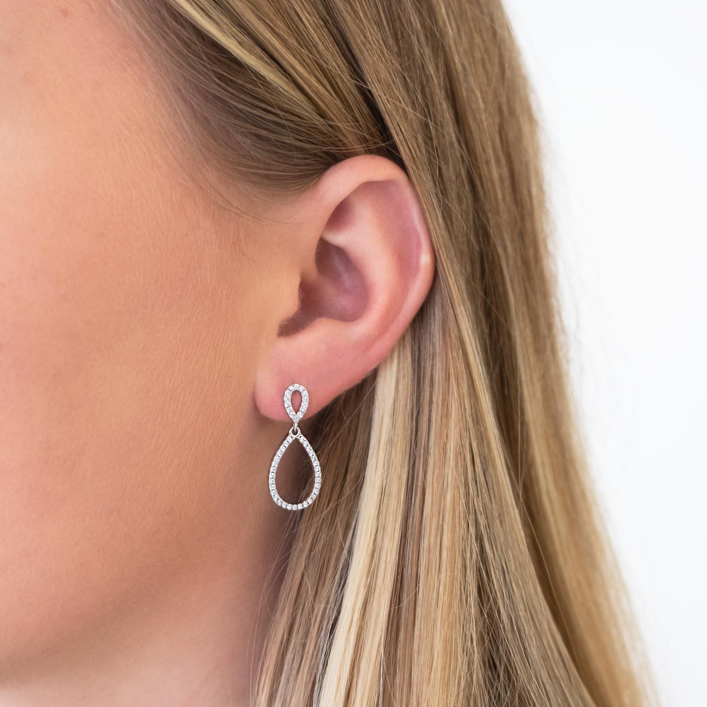Vrouw met blonde haren draagt sterling zilveren oorbellen in het oor