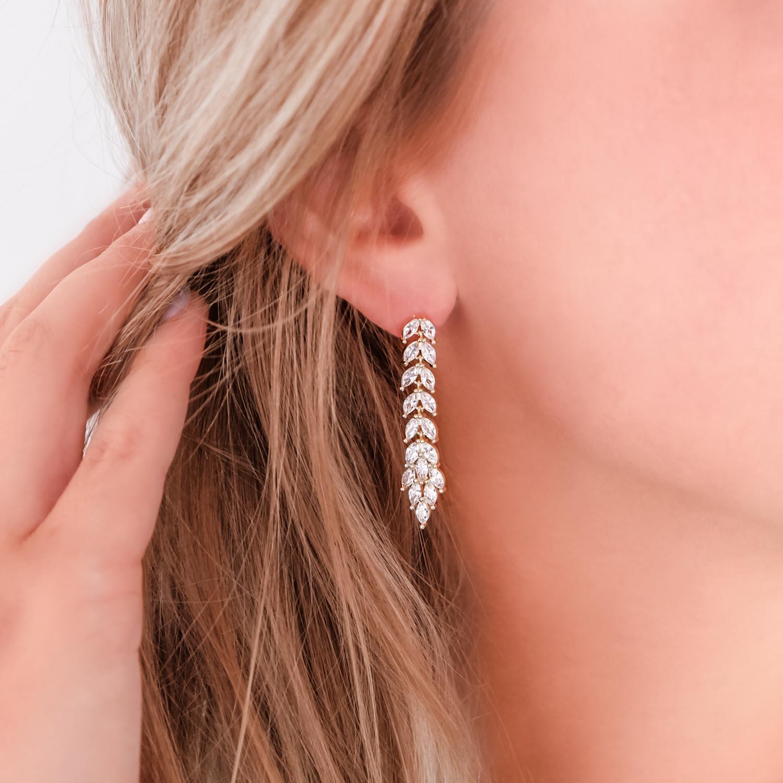 Vrouw draagt goud kleurige bruids oorbellen in oor