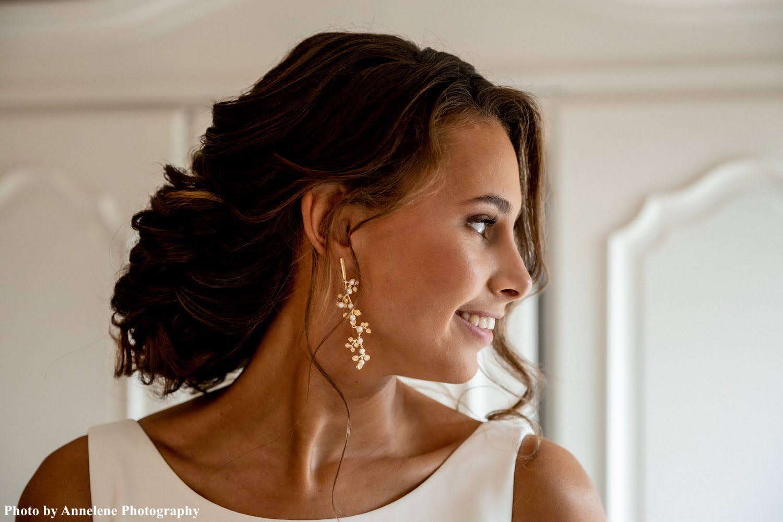Bruid draagt gouden bohemian oorbellen