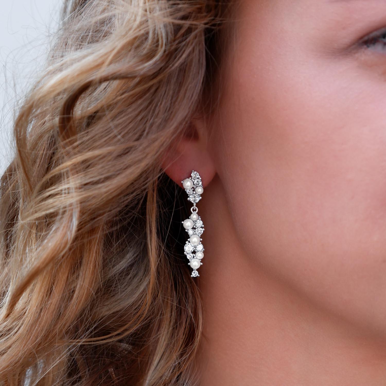 Oorbellen met sparkle en parels in het oor voor een trendy look